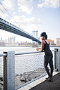 USA, New York City, Brooklyn, woman listening to music near Manhattan Bridge - GIOF03090