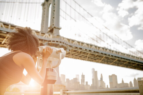 USA, New York City, Brooklyn, woman looking through coin-operated binoculars at Manhattan Bridge - GIOF03093