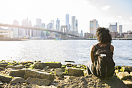 USA, New York City, Brooklyn, woman sitting at the waterfront - GIOF03096