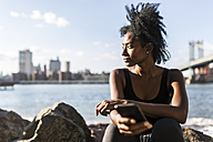 USA, New York City, Brooklyn, woman with cell phone sitting at the waterfront - GIOF03099