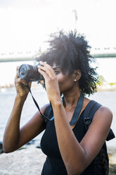 USA, New York City, Brooklyn, woman taking pictures at the waterfront - GIOF03102
