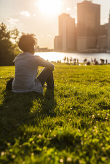 USA, New York City, Brooklyn, woman sitting on meadow looking at the skyline - GIOF03117