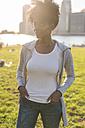 USA, New York City, Brooklyn, woman standing on a meadow - GIOF03120