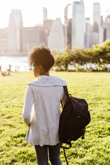 USA, New York City, Brooklyn, woman standing on meadow looking at the skyline - GIOF03123