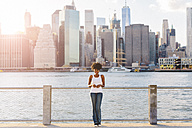 USA, New York City, Brooklyn, portrait of smiling woman standing at the waterfront - GIOF03129