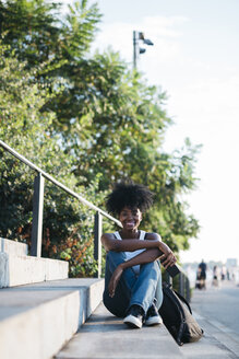 Portrait of smiling woman sitting on stairs outdoors - GIOF03132