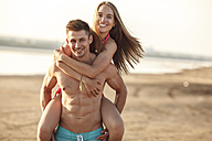 Man carrying his girlfriend piggyback on the beach - VPIF00009
