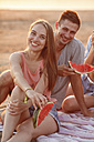 Happy couple with friends on the beach eating water melon - VPIF00021