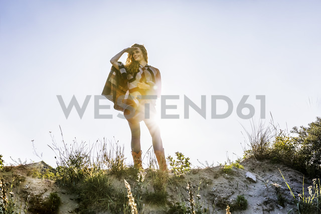 Netherlands, Zandvoort, woman standing in dunes looking out - FMKF04308