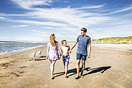 Netherlands, Zandvoort, happy family walking on the beach - FMKF04314