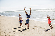 Netherlands, Zandvoort, father with two children doing a handstand on the beach - FMKF04320