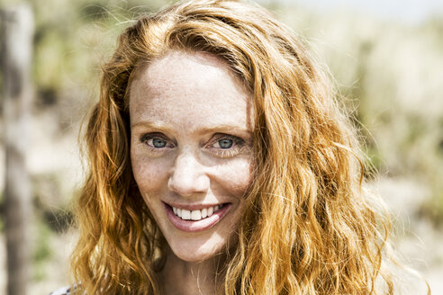 Portrait of smiling redheaded woman - FMKF04326