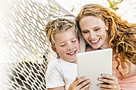 Happy mother and son lying in hammock looking at tablet - FMKF04332