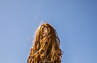 Long red hair covering face of a girl under blue sky - FMKF04344