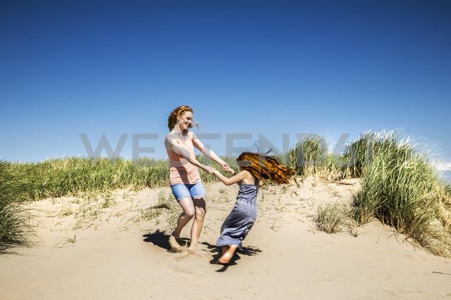 Netherlands, Zandvoort, happy mother and daughter dancing in beach dunes - FMKF04347