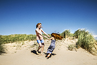 Netherlands, Zandvoort, happy mother and daughter dancing in beach dunes - FMKF04347