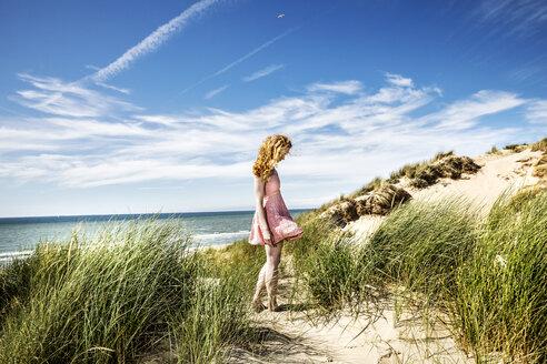 Netherlands, Zandvoort, woman standing in dunes - FMKF04353