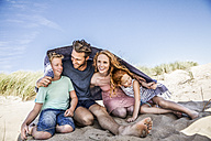 Netherlands, Zandvoort, happy family under a blanket on the beach - FMKF04359