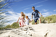 Netherlands, Zandvoort, happy family with daughter in beach dunes - FMKF04362