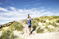 Netherlands, Zandvoort, father carrying daughter on shoulders in beach dunes - FMKF04365
