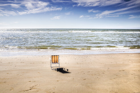 Netherlands, Zandvoort, empty chair on the beach - FMKF04368