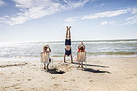 Netherlands, Zandvoort, children clapping hands for father doing a handstand on the beach - FMKF04374