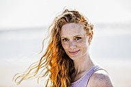Portrait of smiling redheaded woman outdoors - FMKF04377