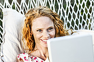 Smiling woman lying in hammock with tablet - FMKF04380