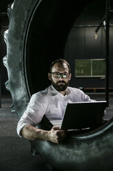 Businessman sitting in truck tire in a gym, using laptop - JOSF01323
