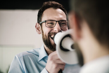 Manager with megaphone giving businessman orders - JOSF01335