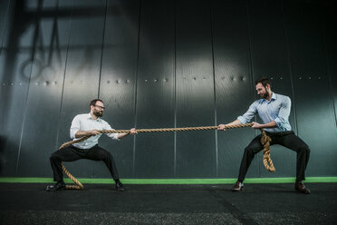 Two businessmen in gym doing tug of war - JOSF01341