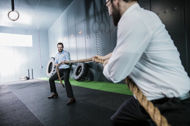 Two businessmen in gym doing tug of war - JOSF01362
