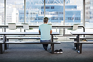 Man working in modern office, sitting on bench, rear view - ZEF14320
