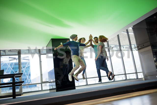 Happy business people high-fiving in office, jumping for joy - ZEF14335