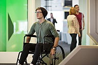 Young man in wheelchair listening to  music in office - ZEF14347