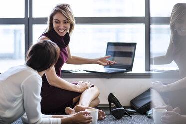 Businesswoman working in office, sitting on floor - ZEF14350