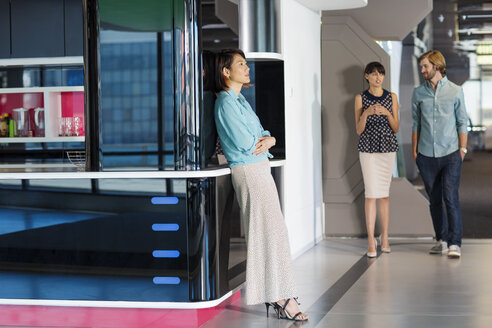 Exhausted businesswoman leaning on wall in busy office corridor - ZEF14398