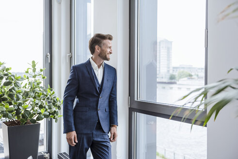 Relaxed businessman standing in his office looking out of the window - DIGF02673