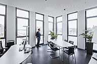 Businessman standing in his office looking out of the window - DIGF02676