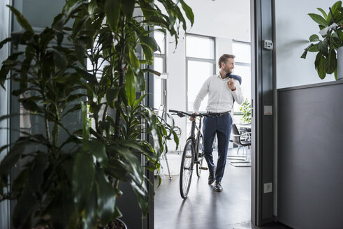 Smiling businessman with bicycle in the office - DIGF02679