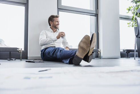 Relaxed businessman sitting on the floor of his office with cup of coffee - DIGF02685