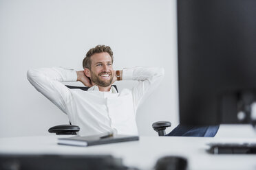 Portrait of content businessman relaxing at desk in his office - DIGF02691