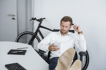 Businessman with earphones sitting at desk with feet up looking at cell phone - DIGF02694