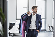 Businessman in office carrying shirts - DIGF02700