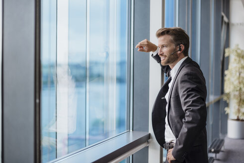 Relaxed businessman with bluetooth headset standing in his office looking out of the window - DIGF02703
