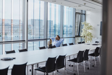 Germany, Berlin, businessman sitting in conference room with feet up looking out of the window - DIGF02712
