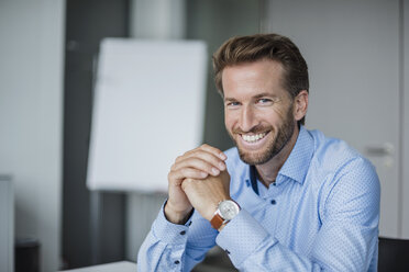 Portrait of laughing businessman in the office - DIGF02715