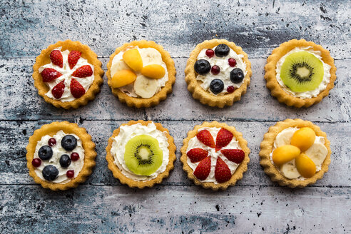 Eight mini pies with whipped cream garnished with different fruits - SARF03355
