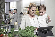 Mother holding baby using tablet in kitchen - ZEF14451