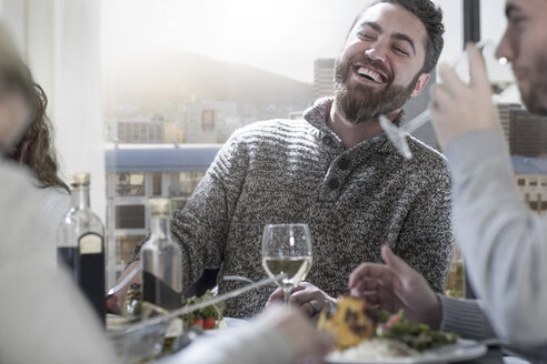 Man laughing at dinner table with friends - ZEF14487